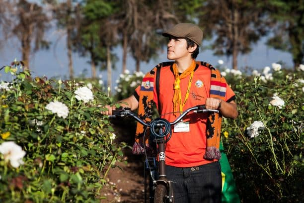 Daiana com bicicleta no campo de flores