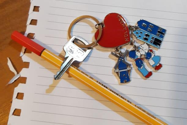 Chaveiro metálico em forma de coração com pendentes de moinho e casal beijoqueiro