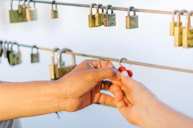 Mãos de Casal colocando cadeado no Deck do Amor