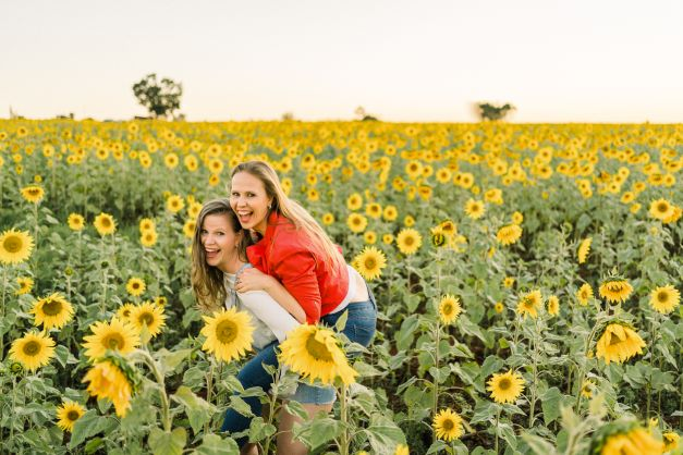 Duas garotas posando no meio dos girassóis