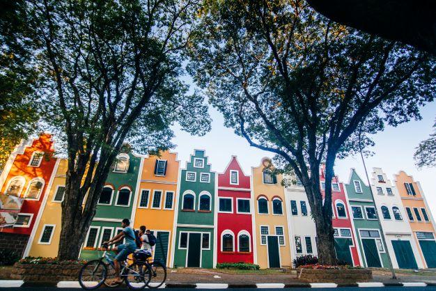 Garotos andando de bicicleta em frente às fachadas coloridas de Holambra