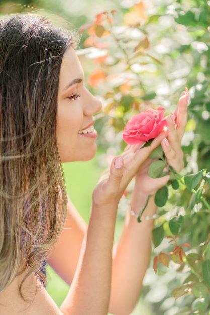 Mulher cheirando uma rosa