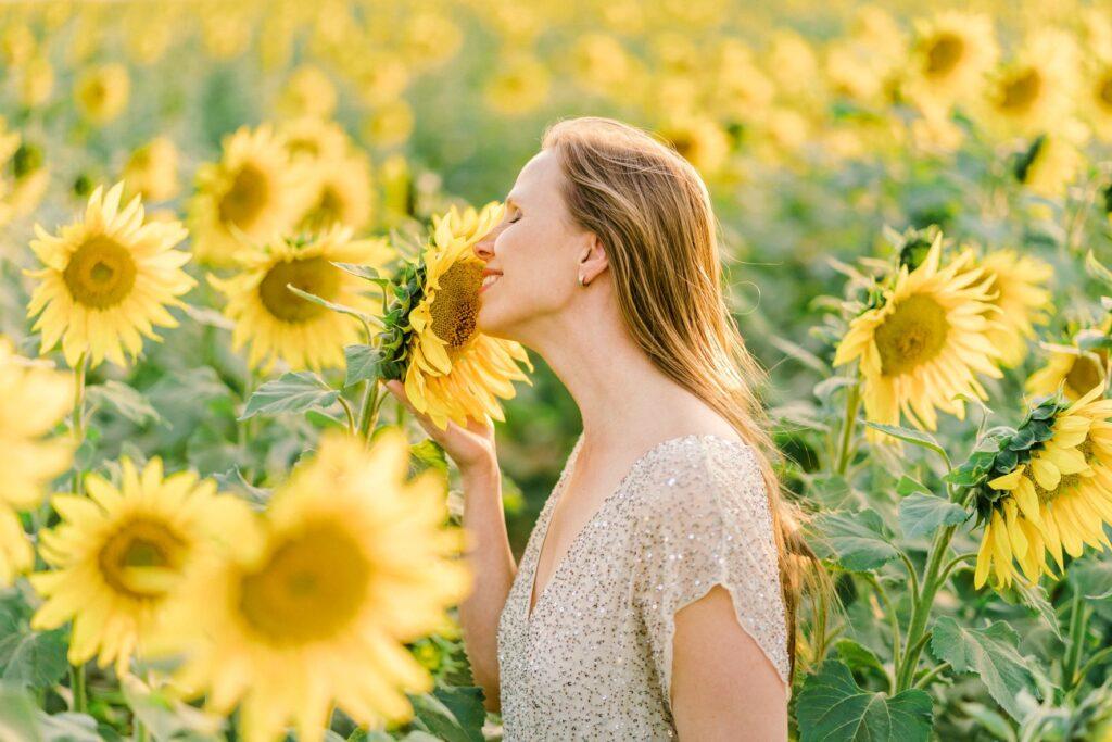 Mulher posando para foto em campo de girassol